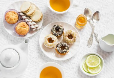 Lemon green tea and sweets - banana muffins, cookies with caramel and nuts, donuts with chocolate and lemon glaze, tea set on white table cloths on a light surface. Tea time. Vintage and rustic style