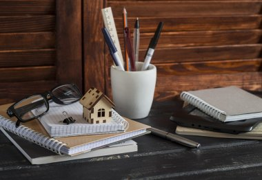 Workplace designer and architect with business objects - books, notebooks, pens, pencils, rulers, tablet, glasses and a model of a wooden house. Planning of the construction of a house.