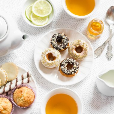 Lemon green tea and sweets - banana muffins, cookies with caramel and nuts, donuts with chocolate and lemon glaze, tea set on white table cloths on a light surface. Tea time.