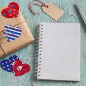 Valentýn dárek v kraftový papír a čisté prázdný Poznámkový blok na modré dřevěného povrchu. Volné místo pro text. Pohled shora