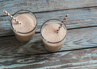 Dulce di leche and ice cream milkshake in glasses on a wooden rustic background