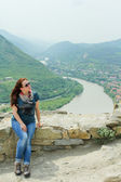 Young woman sitting and  enjoying the view of Mtskheta in Georgia