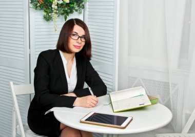 Smiling therapist taking notes on white background