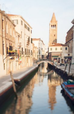 Tilt shift photo of Venice street with boat and tower. Soft focus