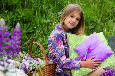 Family picnic. Basket with flowers and next to a beautiful little girl with cushions