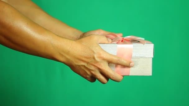 Muž dává dárkové krabice pro někoho se zeleným pozadím, natáčení ve studiu