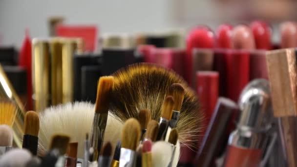 Na stole v salonu krásy velký výběr make-upu štětce, pohyb fotoaparátu.