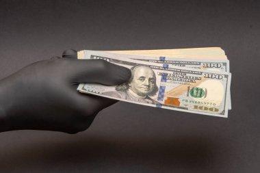 Tıbbi kauçuk eldivendeki bir el bir tomar dolar tutar, seçici odaklanma, yakın çekim. Konsept: Coronavirus salgını sırasında nakit ödeme, güvenli para transferi,