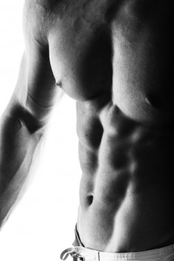 Close up of muscular bodybuilder guy doing exercises with weights isolated on white. Monochrome