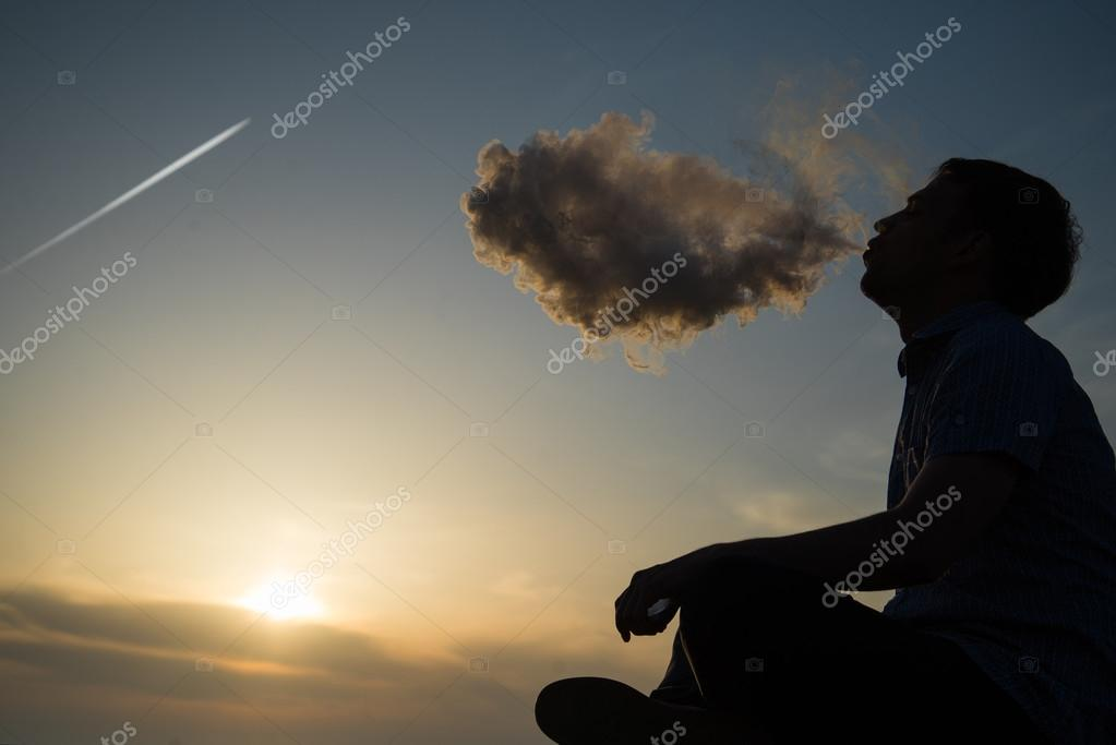 Silhouette of man smoking a pipe in cap at sunset. Photographer in a baseball cap smoking a pipe at sunset by the sea.Travel, adventure, meditation, relaxation, vacation.