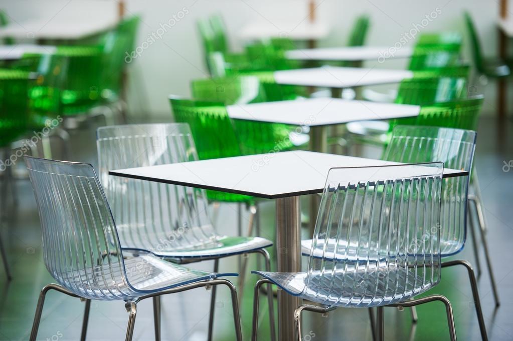 Zona di rstaurant con sedie di plastica colorate e tavoli nella hall ...
