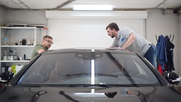 Two specialist dries the car from moisture, car washing at detailing service.