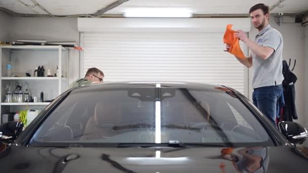 Dva specialisté vysuší auto z vlhkosti, mytí aut na detailní servis.
