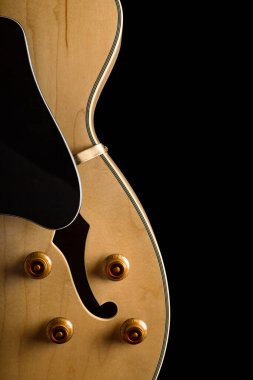 Pale wood guitar on left side of image with buttons and white pickguard of image with buttons and white pickguard