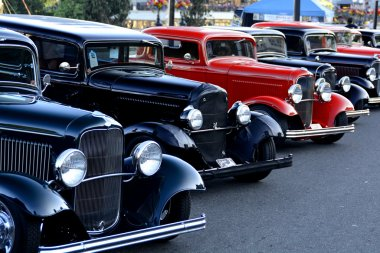 Classic cars lined up on street.