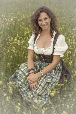 Frau mit Dirndl in Blumenwiese