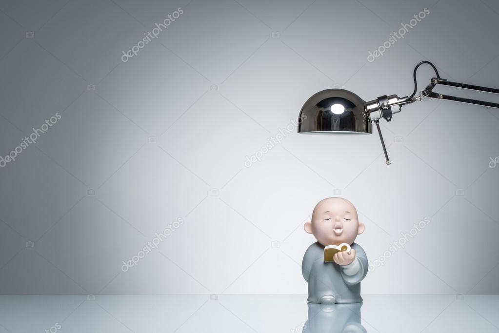 Illuminazione per studiare lettura monaco buddista con lampada da