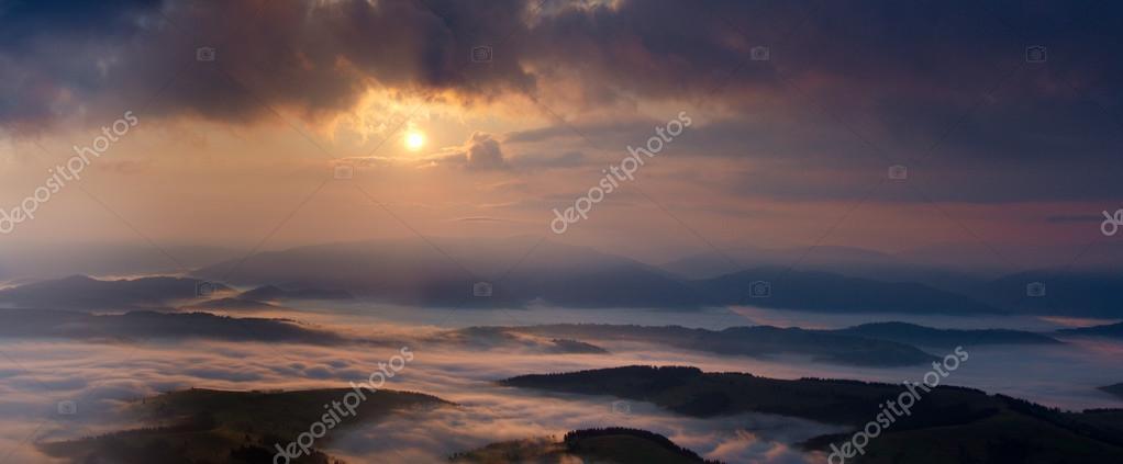 Misty sunrise in Carpathian Mountains panorama