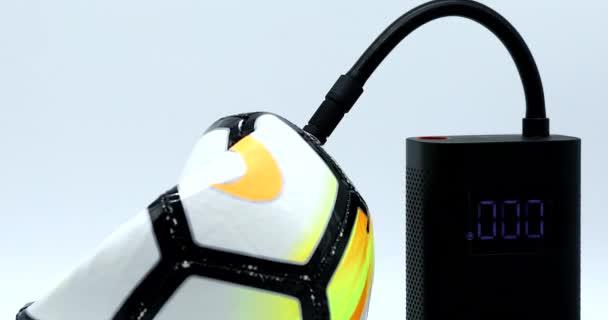 Paříž, Francie - 1. prosince 2020: Nike Soccer Ball Inflated with Mi Přenosný elektrický vzduchový kompresor (Xiaomi Air Pump). Pohled zblízka, makro snímek - rozlišení DCi 4K