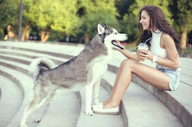 girl drinking ice coffee and playing with her husky dog in the park