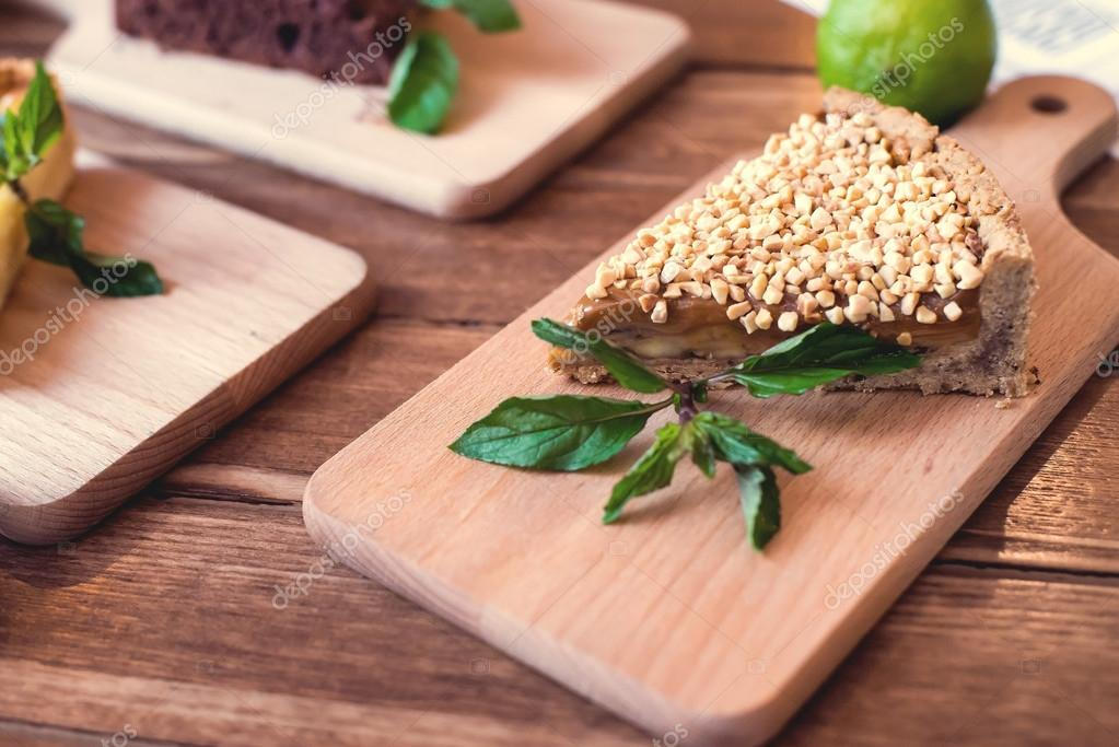 Pieces of nut cake decorated with mint and lime on wooden table