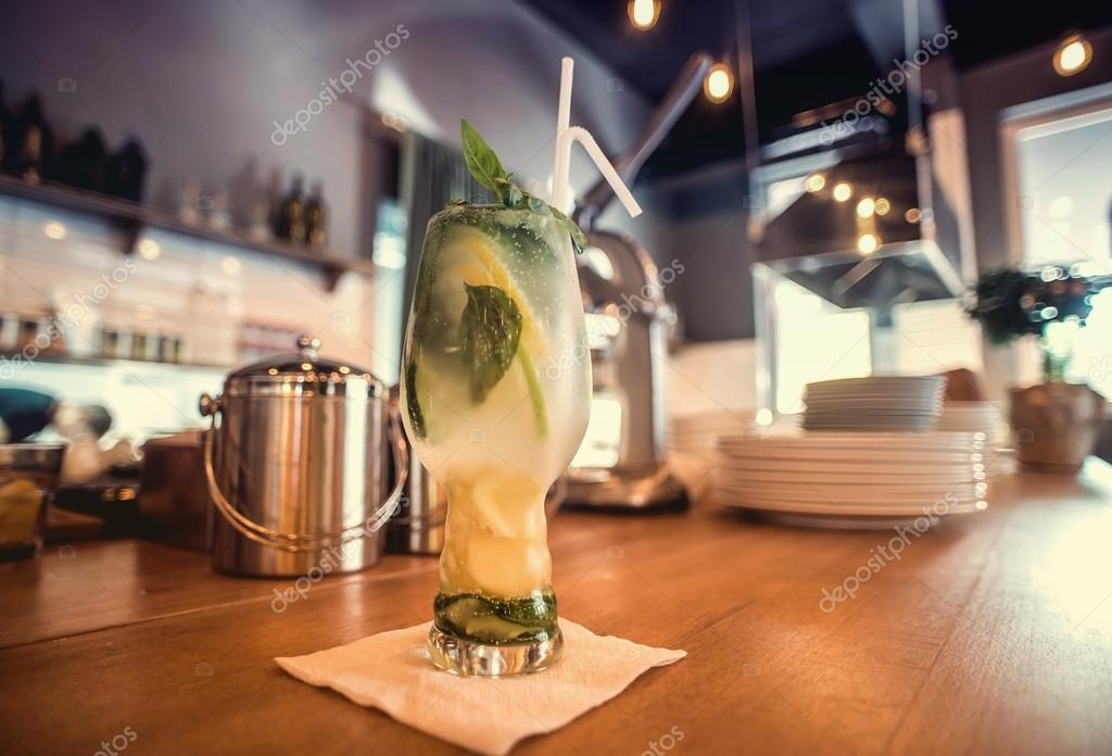 Glass of cocktail with lemon and mint on table