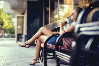 Outdoor closeup portrait of pretty stylish fashion girl having fun drinking chocolate milkshake in a cafe outdoors.