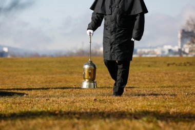Undertaker carrying an urn with ashes of cremated human