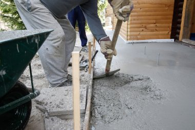 Masons filling wood form with a shovel of concrete mix