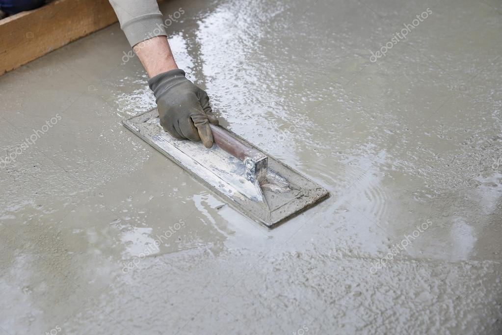 Mason leveling and screeding concrete floor base stock photo mason leveling and screeding concrete floor base with square trowel in front of the house construction business do it yourself precision work around the solutioingenieria Image collections