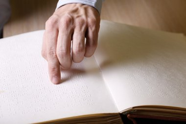 Blind person touching book, written in braille writing