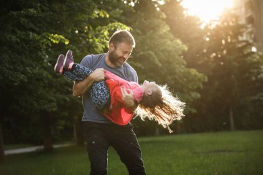 Devoted father spinning his daughter in circles
