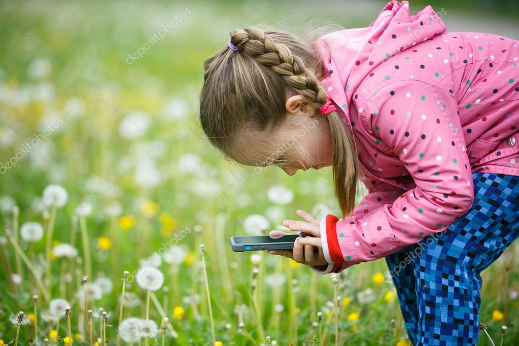 Little girl photographing with her smartphone