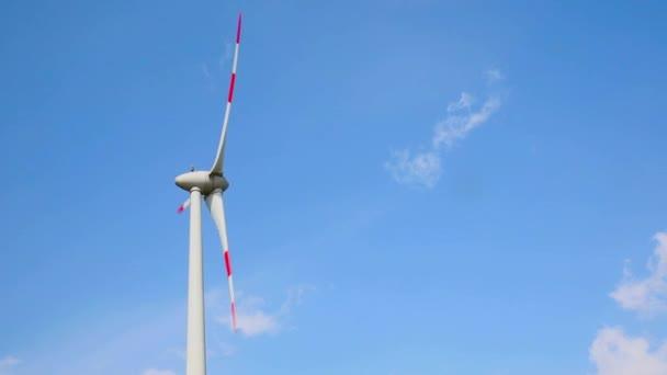Windkraftanlage vor blauem Himmel und weißen Wolken