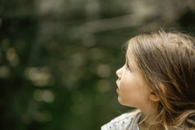 Little girl watching trees, skies and birds in awe