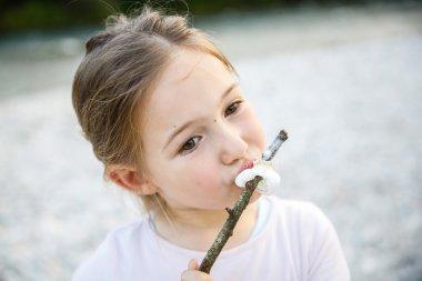 Little girl eating roasted marshmallow