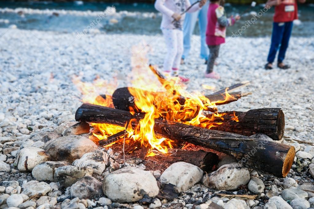 Family enjoying time by the river and self-made campfire