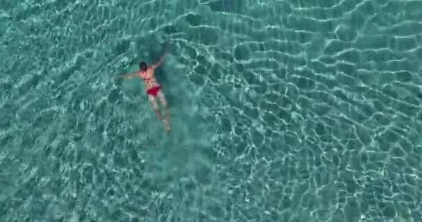 Légi felvétel nő, friss, elképesztően türkizkék tengervíz, úszás élvezi a nyár, a nap és a homok.
