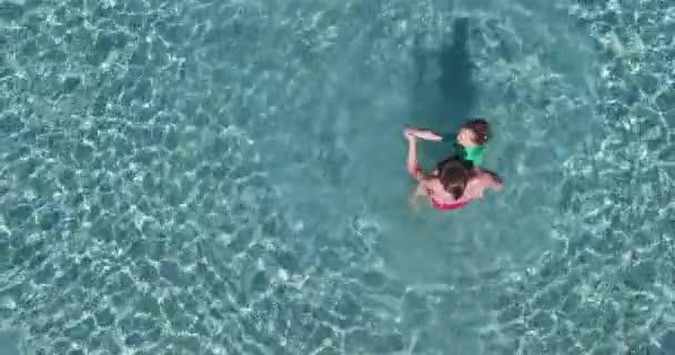 Légi felvétel anya és lánya játszik, és élvezi a gyönyörű és tiszta egzotikus türkizkék tenger vizein, jól érzik magukat a nyári vakáció.