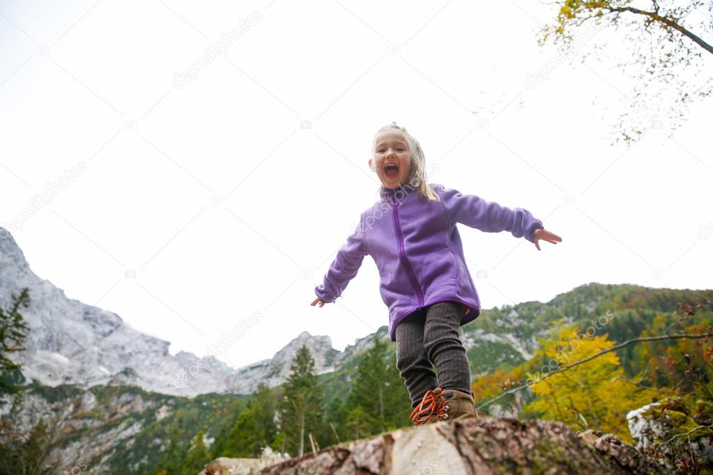 Triumphant little girl celebrating after climbing a rock