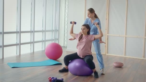 Ärztin hilft schwangerer Frau bei Ballübungen