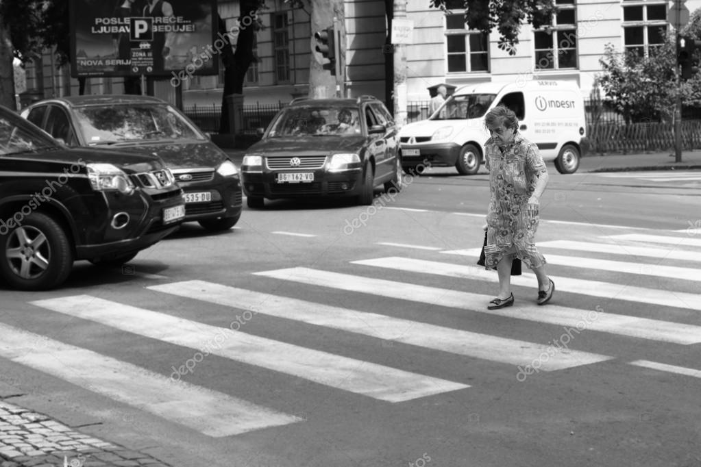 An elderly woman crosses the street on a crosswalk with many cars stops