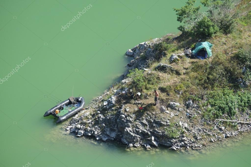 Aerial view of a fisherman and his rubber dinghy and his bivouac in the Uvac Special Nature Reserve near Sjenica in Serbia