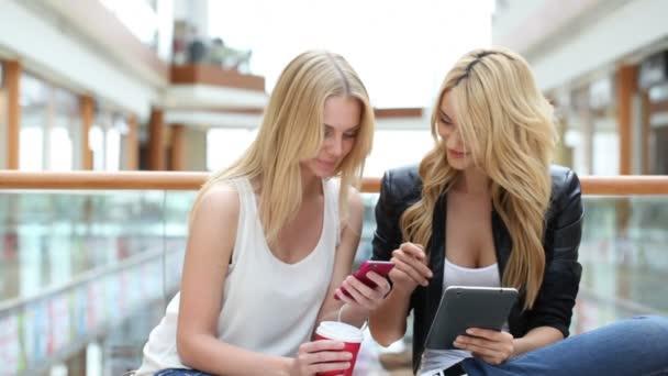 Ženy v obchoďáku pomocí smartphone