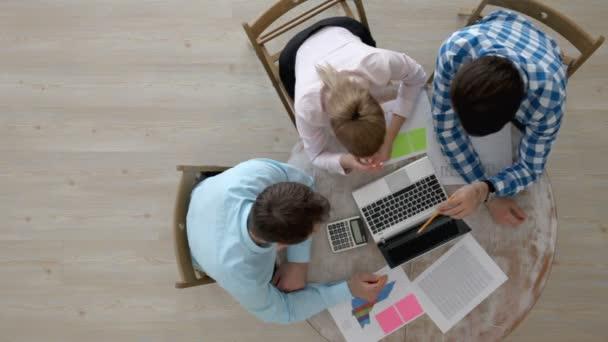 Lidé pracují s notebookem a dokumenty