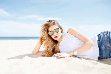 Attractive girl in sunglasses posing lying on the sea beach on a