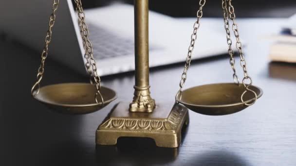 Kancelář právníka se stupnicí, notebookem a dokumenty na pracovišti.