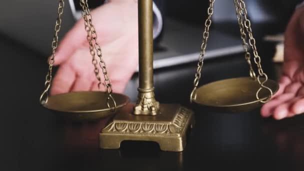 Die Hände des Anwalts halten an und wiegen die Waage