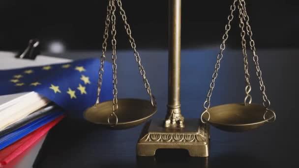 Flagge und Waage der Europäischen Union am Arbeitsplatz des Rechtsanwalts oder im Büro.