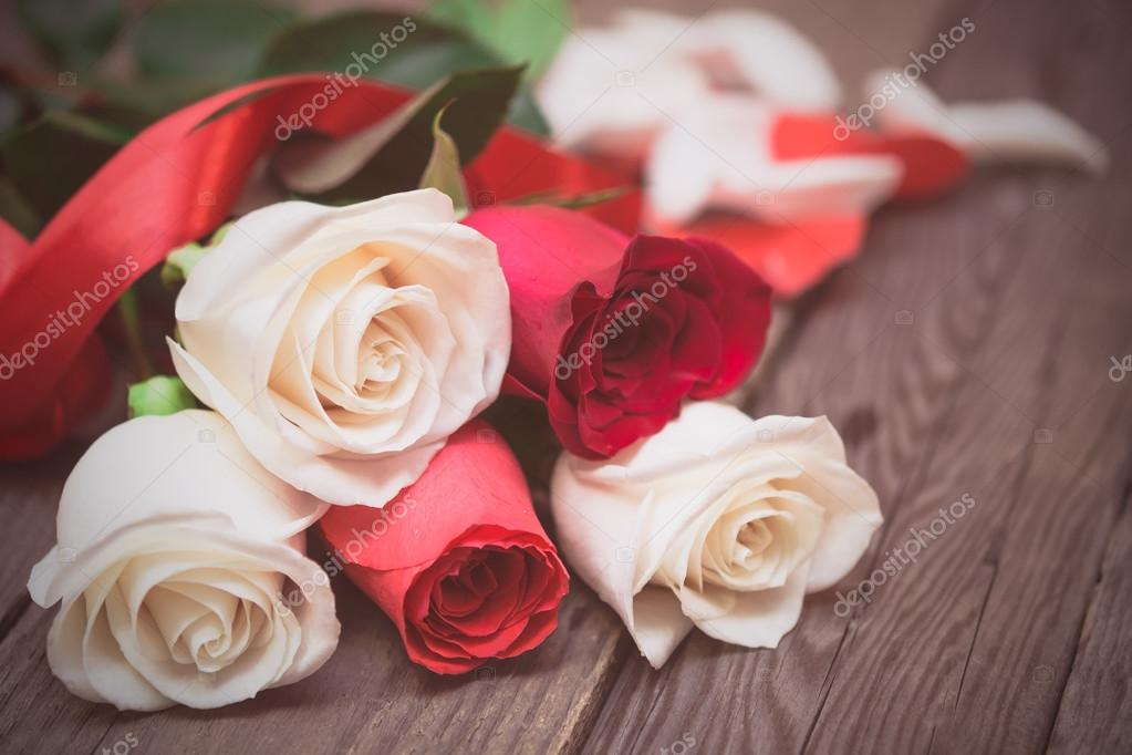 Red and white roses on a dark wooden background. Women' s day, V